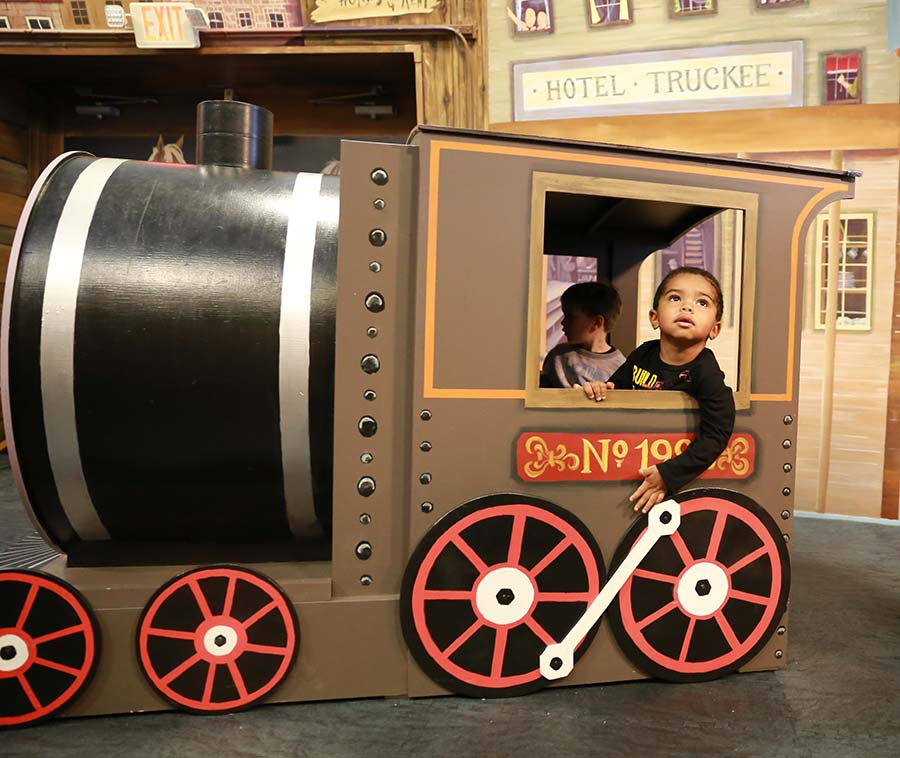 Child playing on sierra settlers train exhibit