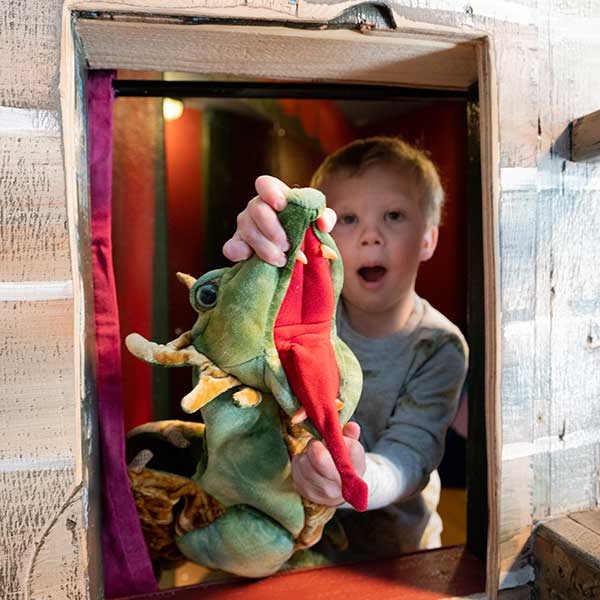 Boy playing with a stuffed dragon at the kidzone museum